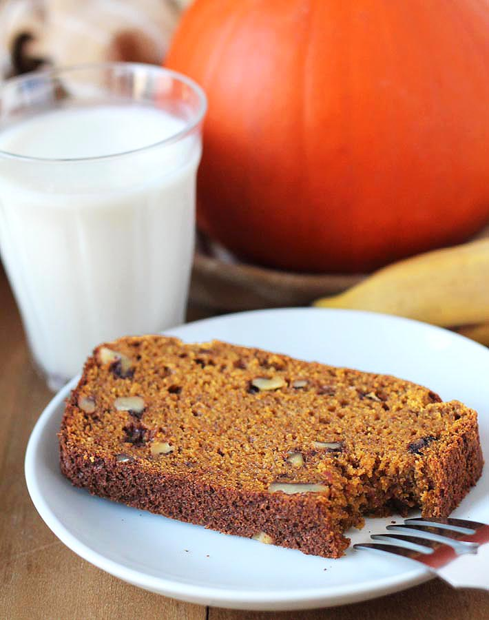 A slice of Vegan Gluten Free Pumpkin Banana Bread on a plate with a forkful taken out of it, fork is sitting on the side of the plate, a glass of almond milk is sitting to the left behind the plate.