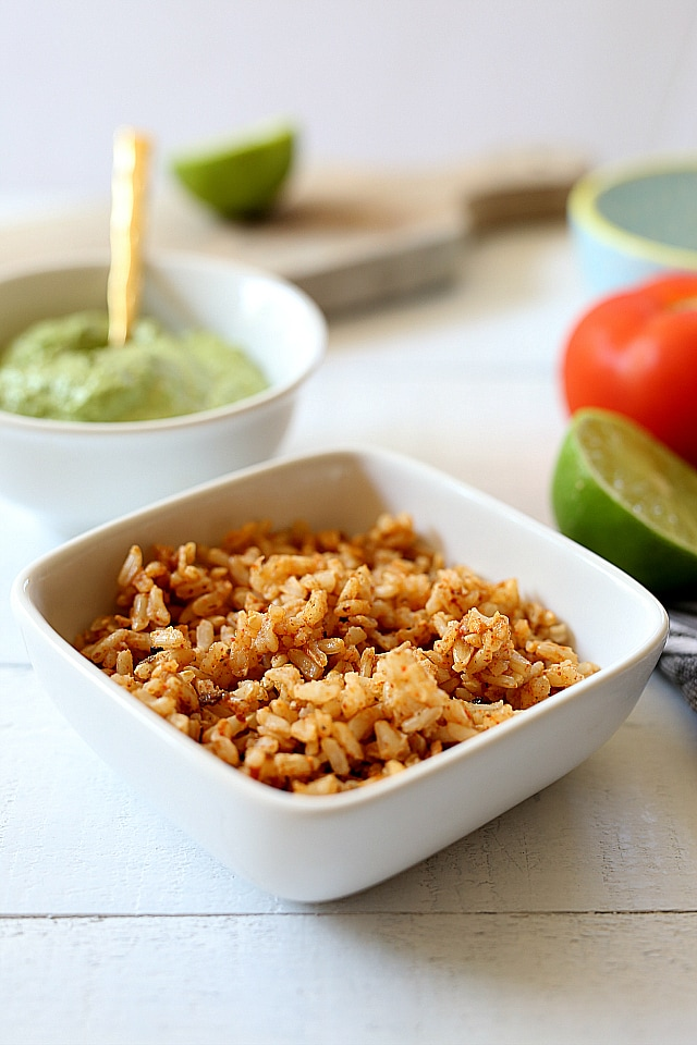 Spanish rice, beans, cheese, lettuce, cilantro and tomatoes stuffed into hard shell tacos and topped with a creamy green vegan sauce. Super easy and healthy recipe for hard shell tacos in under 30 minutes