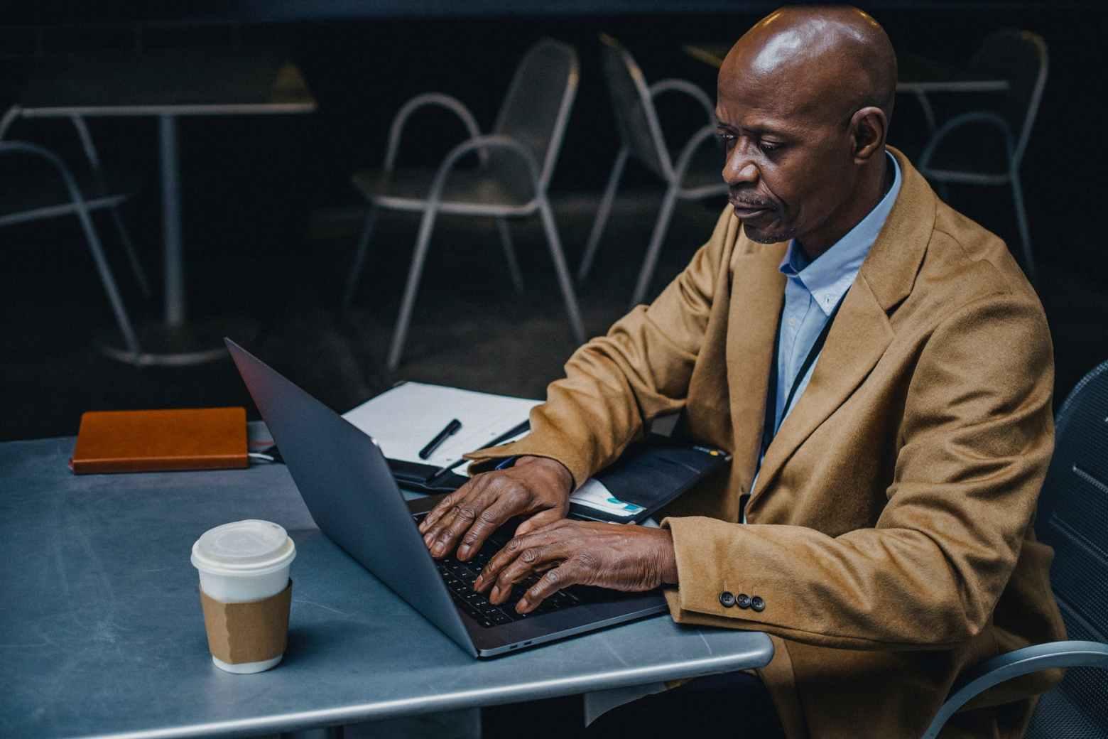 black man typing important information on laptop