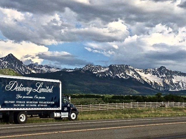 Moving truck on the side of the road with Colorado mountains in the background