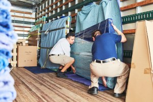 Two movers loading furniture into a moving truck