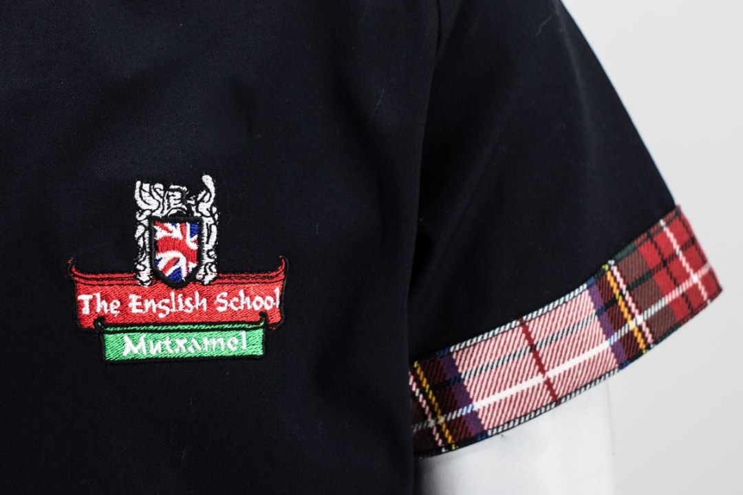 bordado en el pecho en un vestido de uniforme escolar fabricado por delmapunto