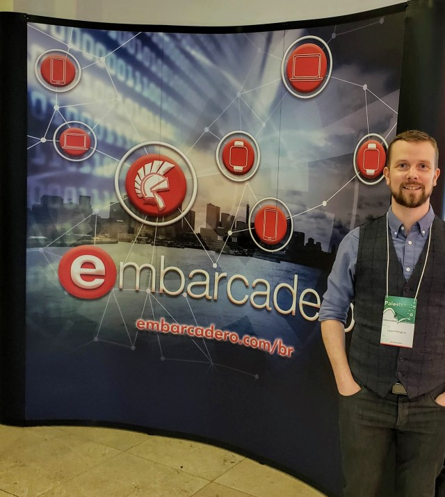 David Millington in front of a sign that says Embarcadero.com/br with a cityscape and reg icons for Delphi and different mobile and desktop platforms