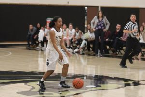 Tiara Tucker dribbles past half court as coach Johnson and team looks on at Joseph Blanchard Gymnasium. PHOTO BY RICHARD REYES
