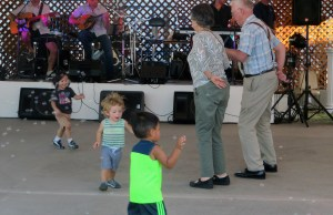 Children blowing bubbles and couple dancing to live band Mythos at Stockton Greek Festival. Photo by Vivienne Aguilar.
