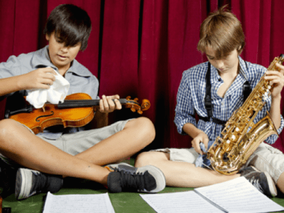 Two boys sit side by side cleaning their musical instruments with cloths.