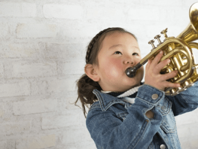 A young girl plays a horn instrument.