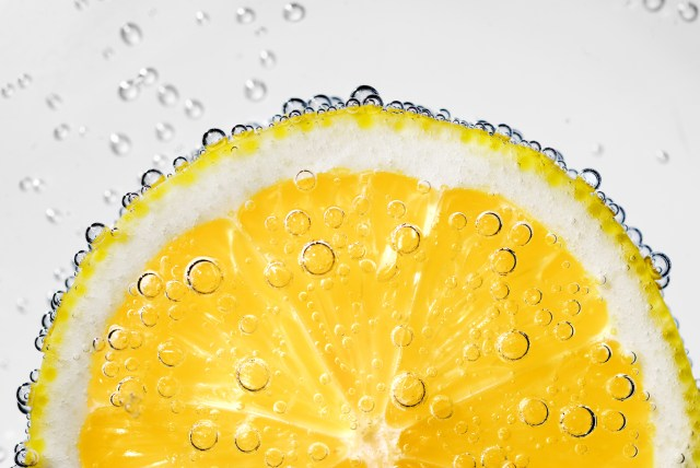 Close up image of a lemon slice suspended in a glass of sparkling water
