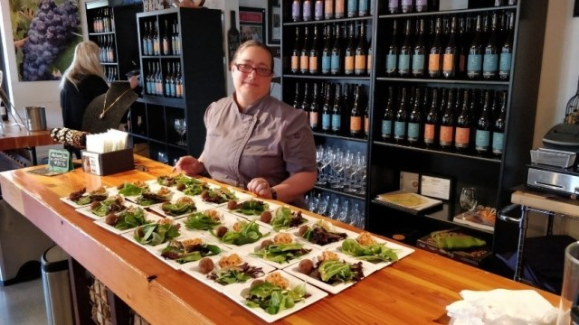 Caterer Jennifer Johnson of Witnessing  Nature in Food stands behind plates of prepared salads