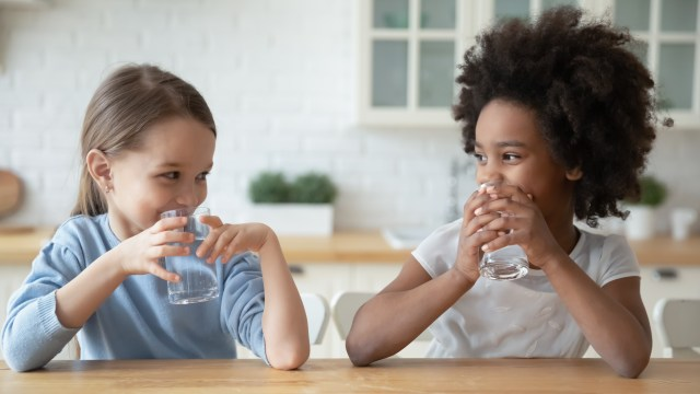 kids smiling and drinking water for good oral health