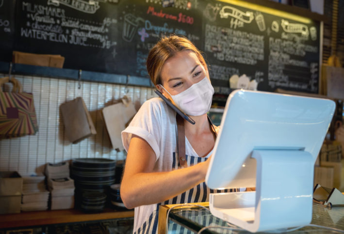 waitress working at a restaurant wears a face mask as she takes an order over the phone