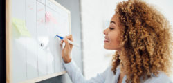 Professional woman standing near a whiteboard and checking items off her to-do list that will help her employees budget for dental care