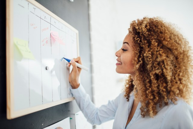 Professional woman standing near a whiteboard and checking items off her to-do list to help her employees budget for dental care