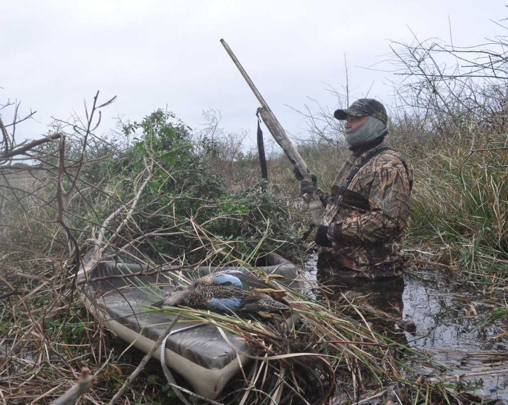 Steve Biggers hunting teal ducks. Hunter standing in wetlands with blue teal ducks displayed on the bow of the boat