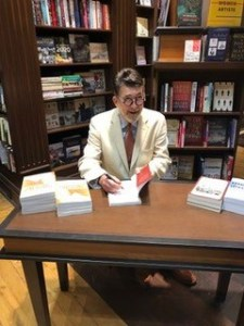 Photo from the book launch of Death of a Butterfly: Mental Health Court Diaries from Septepber 11, 2019 at Ben McNally Books. Richard D. Schneider sits at a table, signing copies of his book.