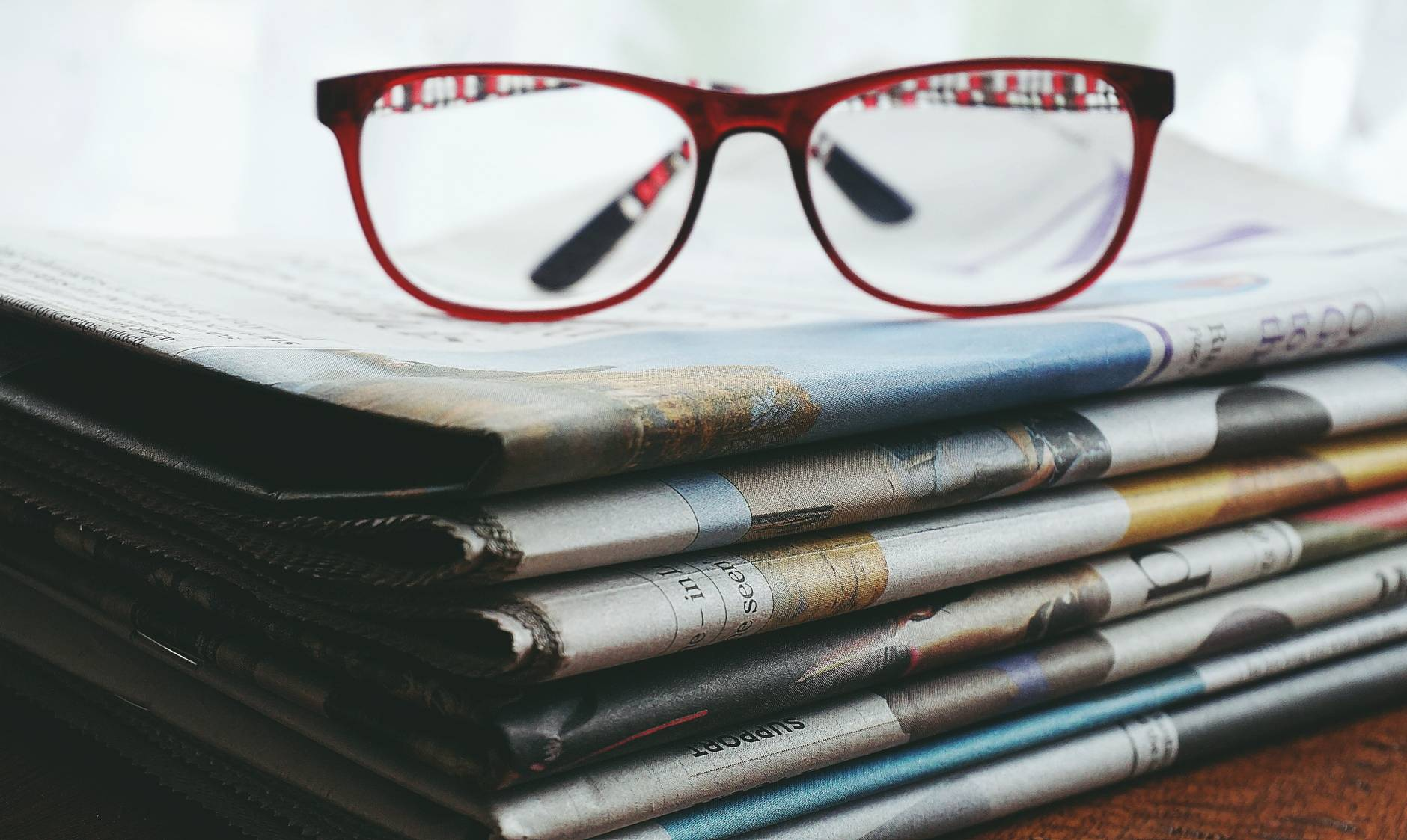 red framed eyeglasses on newspapers