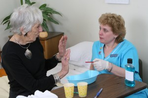 Person with dementia refusing care while caregiver uses strategies to gain cooperation.