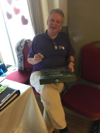 A happy trustee - pork pie in one hand and a raffle prize in the other!