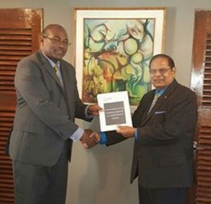 Head of the steering committee on constitutional reform, Nigel Hughes (left) delivering the report to Prime Minister Moses Nagamootoo.