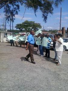 Minister of State, Joseph Harmon being greeted by supporters who held pro-Harmon placards.