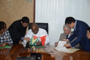 Minister of Finance, Winston Jordan, and outgoing Ambassador of the People's Republic of China, Zhang Limin signing the Framework Agreement for the East Coast Road expansion at the Ministry of Finance