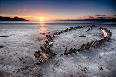 Rossbeigh Strand, Ireland. The old wreck of the Sunbeam buried in the sands of Rossbeigh at sunset.