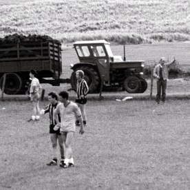 Coal tractor load of turf rolling past a Gaelic football match