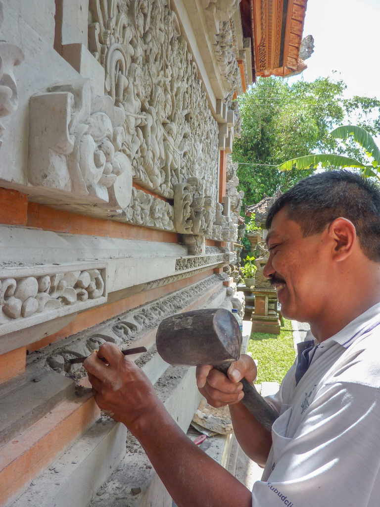 A craftsman at work - many Balinese houses have beautiful artwork on the outside.