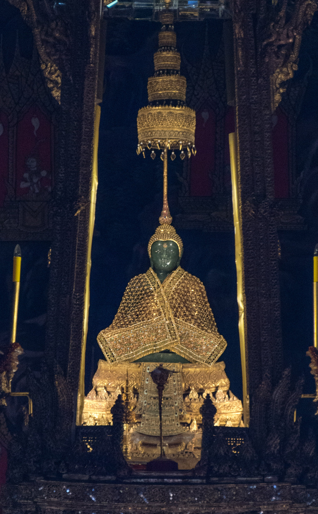 The famous Emerald Buddha in the Royal Palace, Bangkok. The Buddha is actually made of jade; it was found in 1434 in Chiang Ria where it was hidden. According to legend, the Emerald Buddha was created in India in 43 BC. The Emerald Buddha gets new clothes three times per year in a big ceremony involving the King; it is now wearing its winter clothes. Photography not permitted inside so Karel took this shot from outside the building at a great distance from the Emerald Buddha.