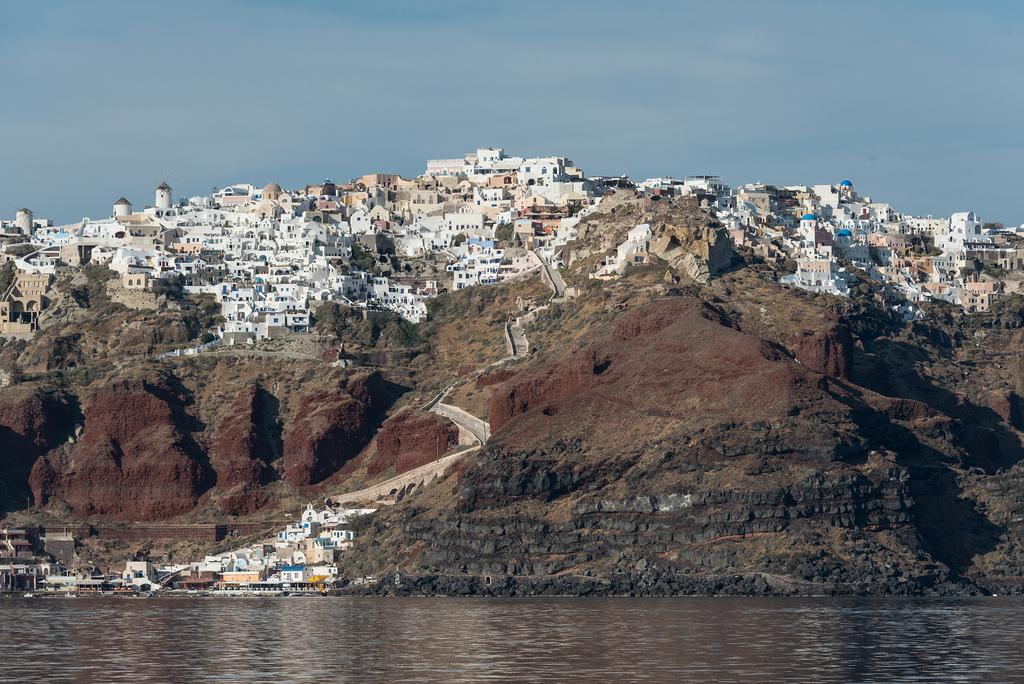 Fira, de hoofdstad van Thira (Santorini), gezien vanuit het water. U kunt Fira met de auto op de achterkant van de velg bereiken, maar als u het water wilt halen, zijn uw beste mogelijkheden om een muilezel te rijden of de kabelbaan te nemen.