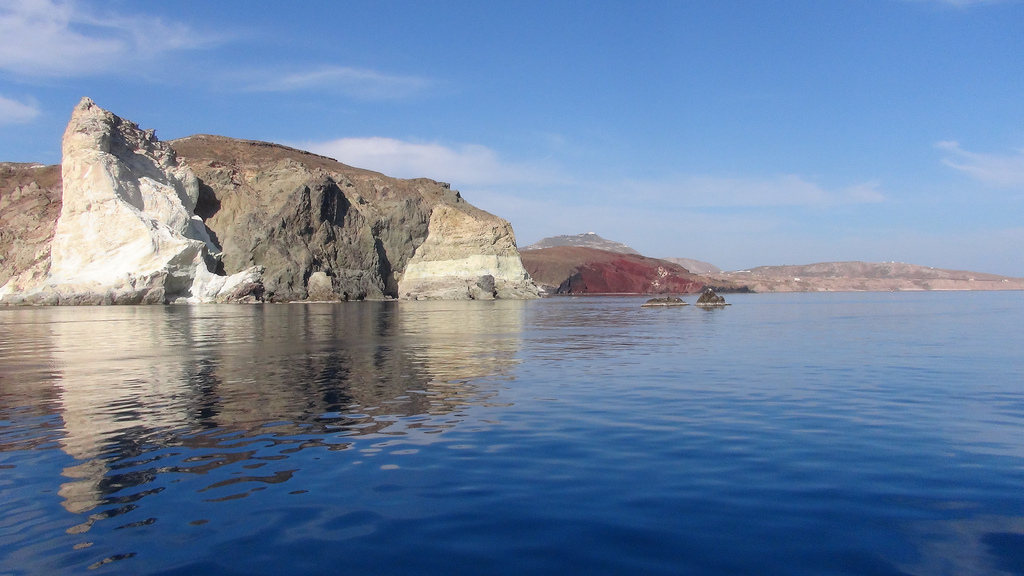 De multi-layered gekleurde rotsen van de Thira kust.