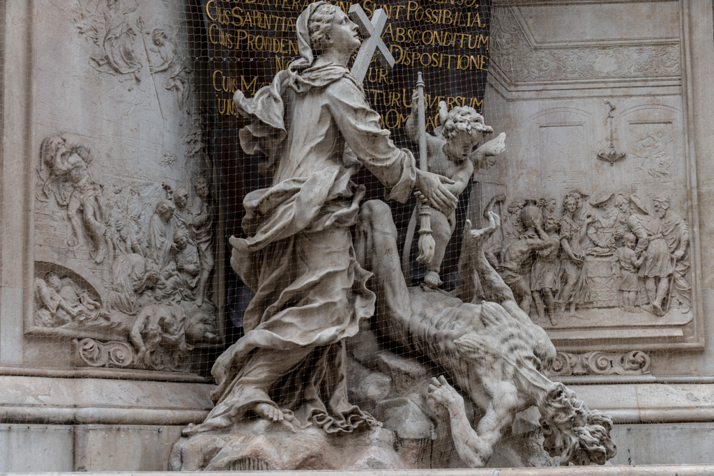 Remembering the Great Plague. The lowest level of the monument shows an angel vanquishing the disease, in the form of a hag.