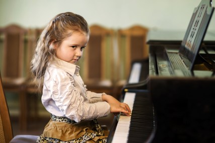 Cute little girl playing grand piano in music school childhood concept