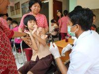 Seorang dokter gigi sedang memeriksa anak dengan Sindrom Down