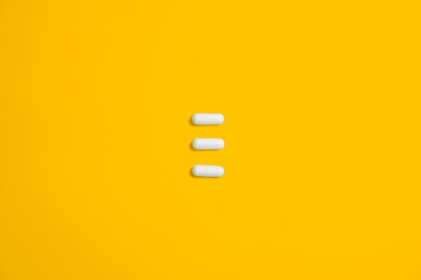white three oval capsule on yellow canvas