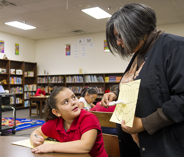 Janie Villarreal shows a student brushing techniques using apaper diagram and toothbrush.