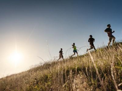 People run in a field.