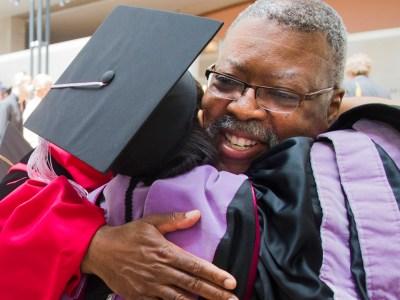 Dr. Reginald Taylor congratulates a student duriung commencement.