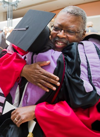 Dr. Reginald Taylor congratulates a student during commenecement.