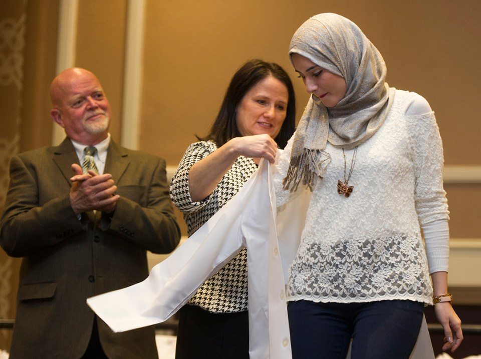 Texas A&M College of Dentistry Alumni Association President Laurie Inglis helps a student into her white coat.