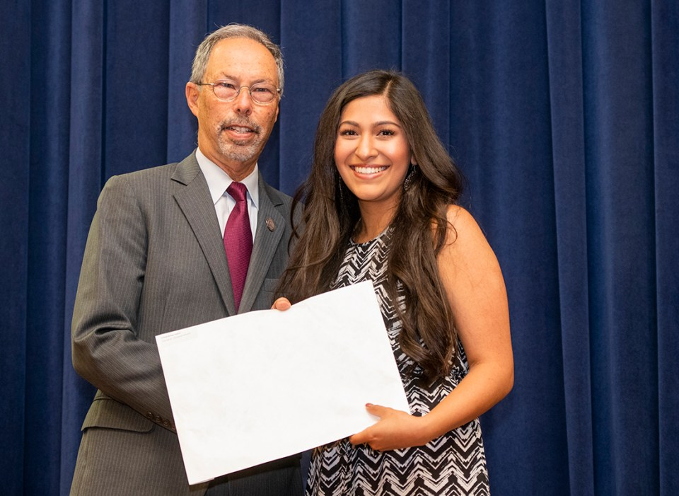 Crystal Cuellar, 2018 Caruth graduate, receives the George B. Clendenin Award from Dean Wolinsky during the college's May 24 student award ceremony.