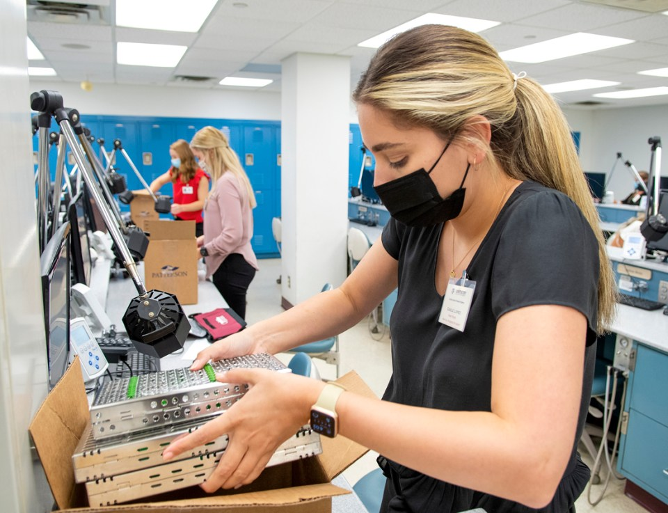 Gisele Lopez, first-year dental hygiene student, unpacks her instruments during orientation.