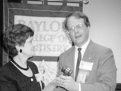 Incoming president Dr. Frank Eggleston accepts the gavel from outgoing president Dr. Bettye Whiteaker at the college's 1991 Alumni Association meeting.