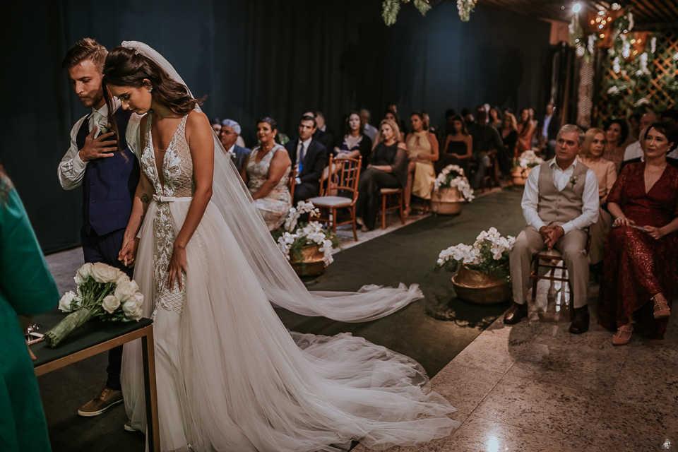 Casal realizando a cerimônia de casamento, e convidados observando sentados.