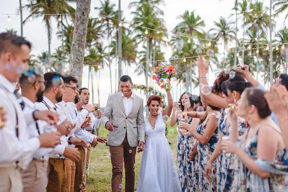 Noiva e noivo caminhando por um corredor de padrinhos e madrinhas no campo.