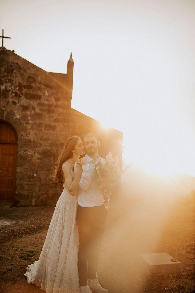 noivos posam no alto de um monte de frente para uma capela - fotos pós wedding