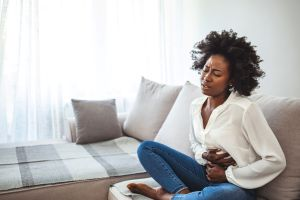 woman sitting on couch holding stomach in discomfort