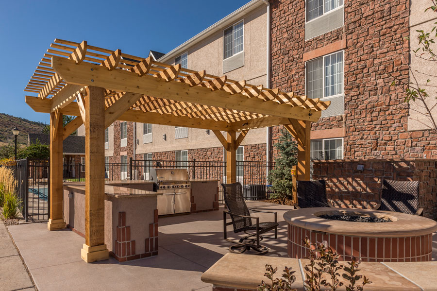 outdoor room fire pit outdoor kitchen pergola stained concrete patio denver landscapes