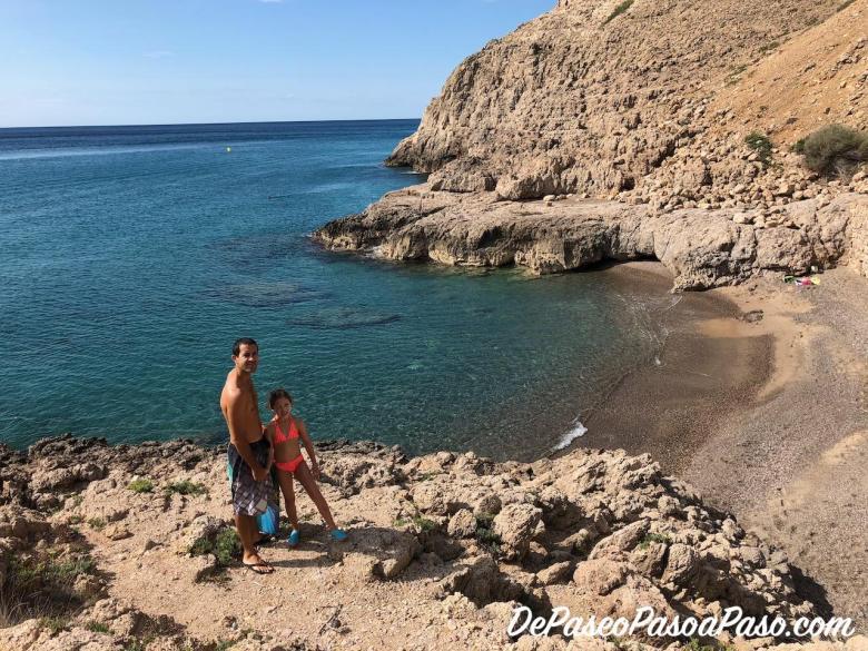 Padre e hija en playa por la que se accede nadando a la Cova del llop Mari