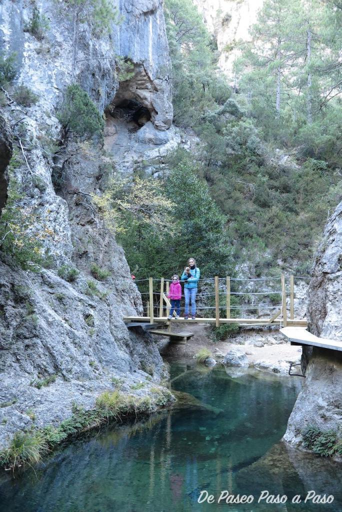 madre e hija en puente de madera sobre río Matarraña